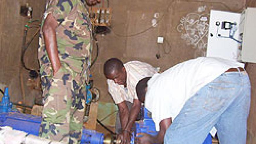 RDF 408 Brigade technicians working on a water pump at Kigarama water source (Photo; A.Gahene)