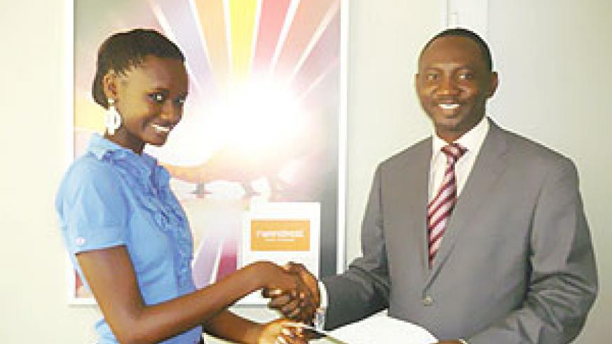 (R-L)Rwandatel's CEO, Issiaka Maiga Hamidou hands over the car insurance documents to Miss Rwanda, Grace Bahati.