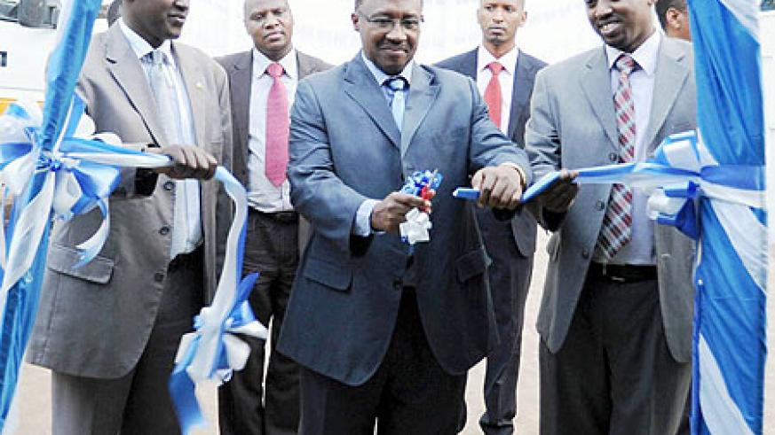 Minister Protais Musoni (C) cutting a ribbon to commission the Rwanda Press Centre yesterday. With him are Patrice Mulama and Arthur Assimwe of the MHC (Photo/ F. Goodman)