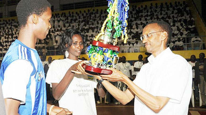 President Paul Kagame receives a trophy from the sports fraternity yesterday. (Photo J Mbanda)