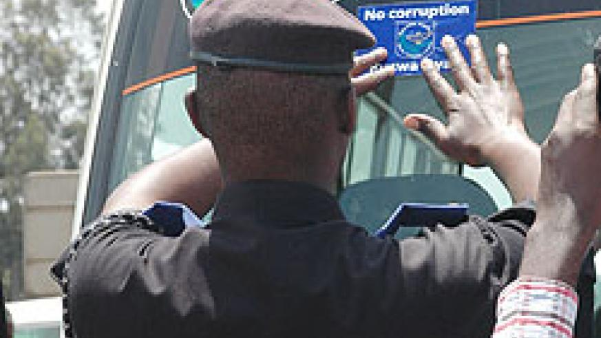 A police officer sticks an Anti-corruption sticker on a passenger van last year. Rwanda has again ranked top in the region for her stance on bribery and corruption (File Photo)