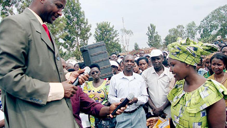 Mayor Neheme Uwimana (L) handing over a cell phone to one of the beneficiaries (Photo: S. Rwembeho)