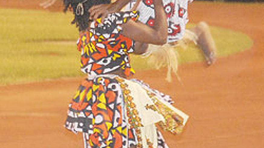 Strong Angolan woman carries a male dancer.