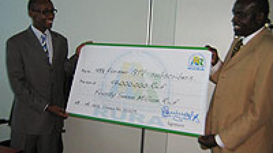 DONE DEAL; Acting DG of RURA, Regis Gatarayiha holds a dummy cheque with J. Kapukha of DN International. The money is meant to compensate all former GTV subscribers (Courtesy Photo)