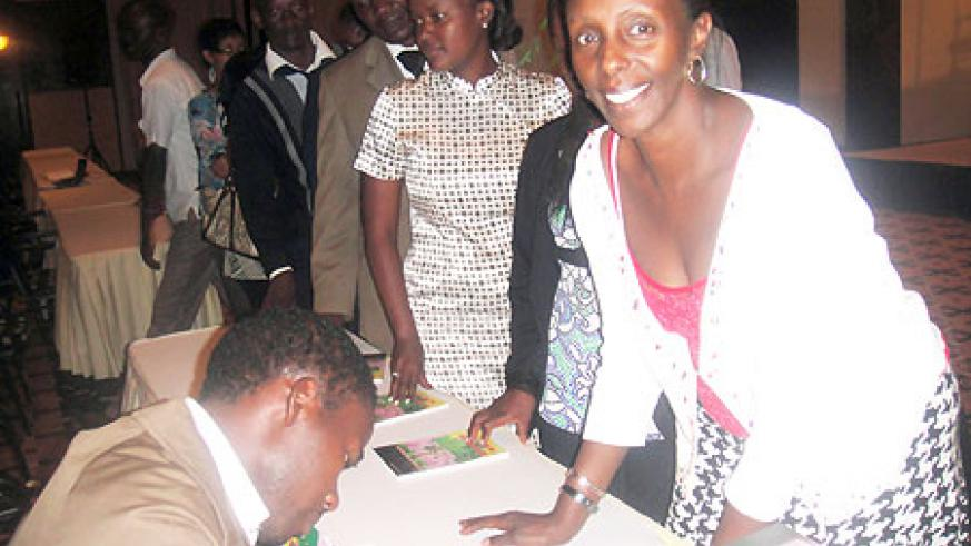 Bamporiki signs autographs after the launch of his book.