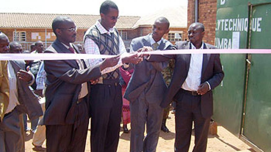 A representative of National Genocide students association (second from left) Clement Kayitakire cuts tape to launch AERG at IPB. (Photo: A. Gahene)