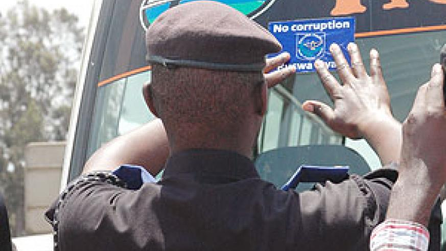 A Police officer puts a No Corruption sticker on a commuter omnibus. Reports have indicated  decreasing corruption cases in the country. (File photo)