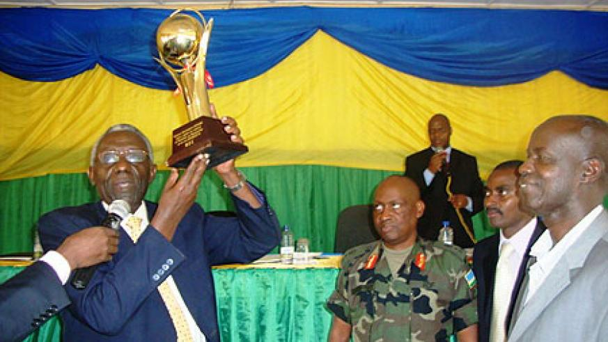 NEC Chairman, Chrysologue Karangwa,  handing over the trophy to Governor Ephraim Kabaija ( Photo by S. Rwembeho)