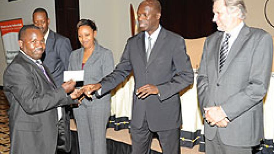 The Minister of Labour, Anastase Murekezi awarding Clement Dusabe of Envirotech (Photo J. Mbanda)