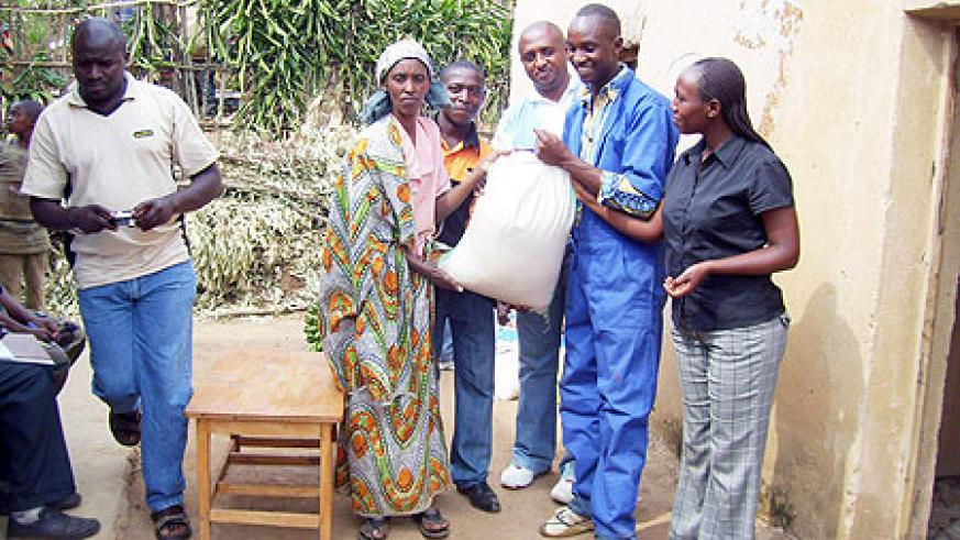RECO-RWASCO staff handing over a bag of rice to Mukashema (C) on Friday ( Photo by A.Gahene)