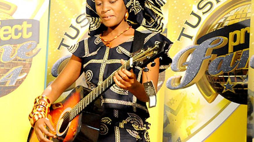Rehema Mukamuganga takes on the stage with her guitar (Photos by F. Goodman).