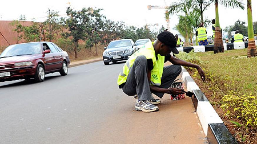 GIVING THE ROADS A FACELIFT; Workers painting Kigali City street pavements ahead of the swearing in ceremony slated for Monday (Photo: J. Mbanda)
