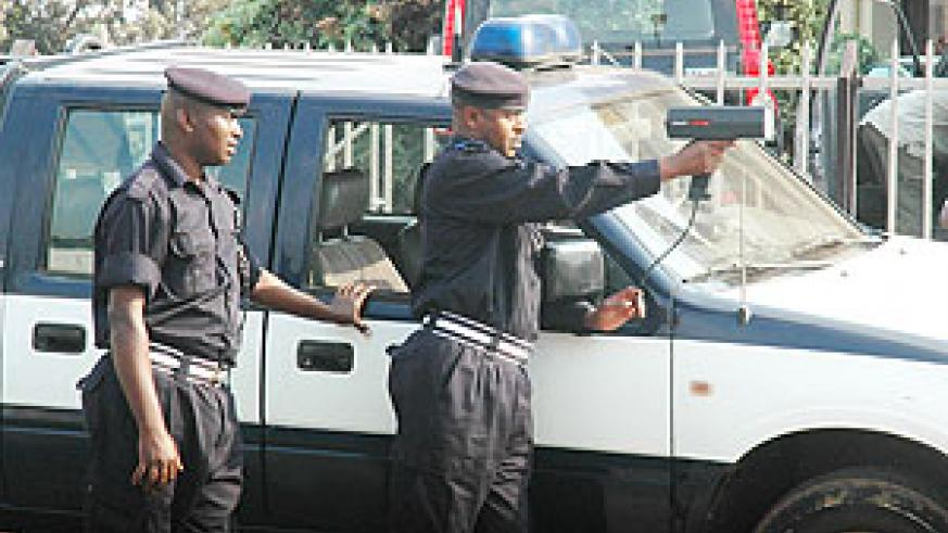 Sup. Benoit Nsengiyumva trains a speed gun on an an approaching car. Police has extended such gadgets to rural areas (File Photo)