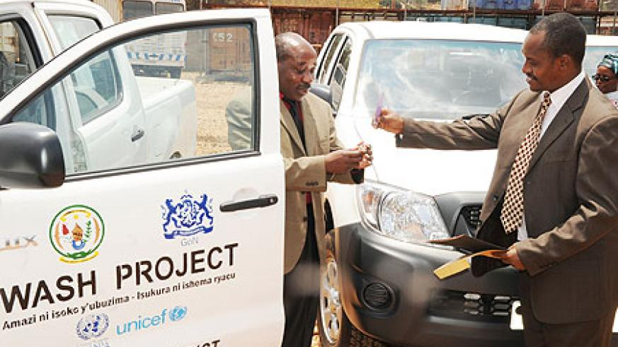 The  Mayor of Burera (l) receiving the keys of the new car fromUNSCO country chief.