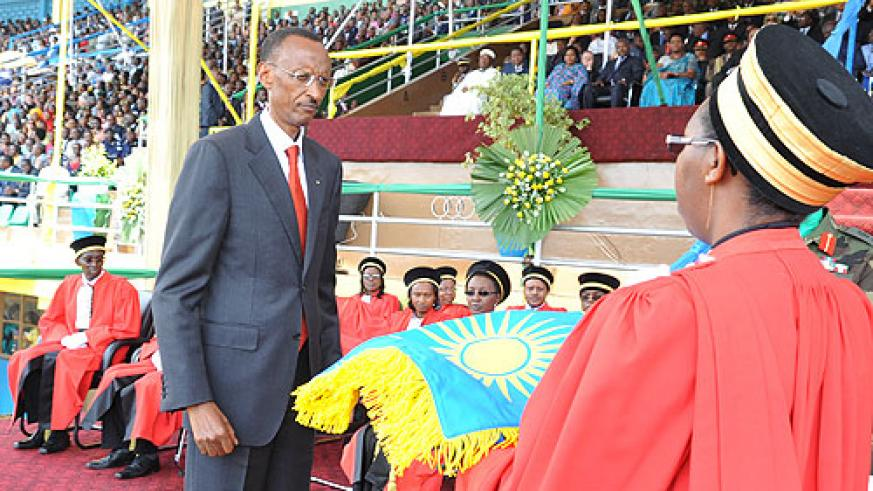 President Kagame receiving the national flag, one of the instruments of power, from Chief Justice Aloisea Cyanzaire, shortly after swearing-in (Photo Urugwiro Village)
