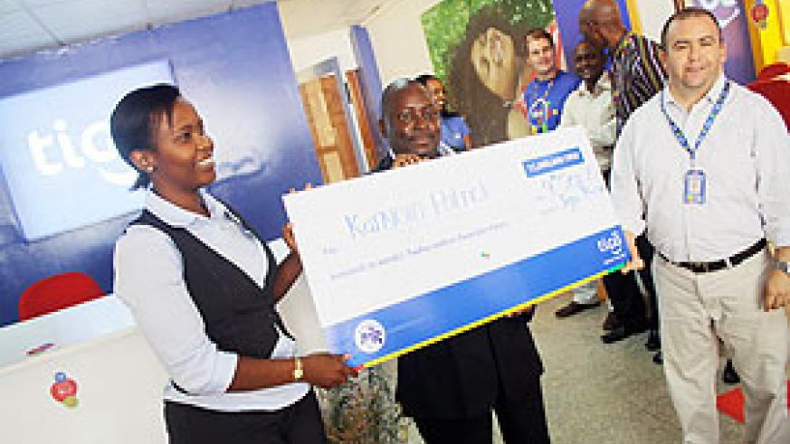 Clare Akamanzi (L) hands over a dummy cheque to Kanyoro (C) as TIGO Rwanda CEO Aleman (R)looks on (Courtesy photo)