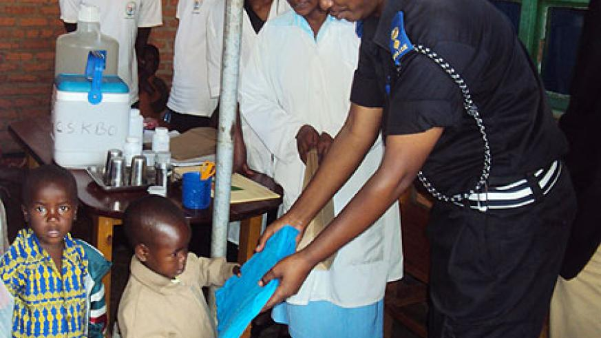 A police officer Supt. Alex Rutabayiro distributes mosquito nets to children in western Rwanda in April this year. File photo