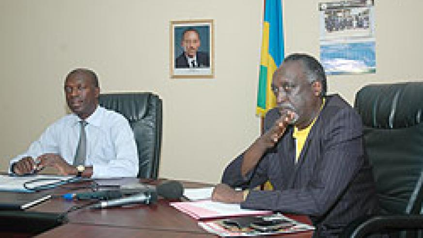 Ombudsman Tito Rutaremara(R) making addressing the media recently as the Minister of Labour and Public Service, Anastase Murekezi looks on (File photo)