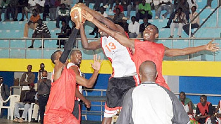 KBC's Fiston Muhire fights for the ball with two Ferwaba Select players. KBC won the contest 81-42. (Photo J. Mbanda)