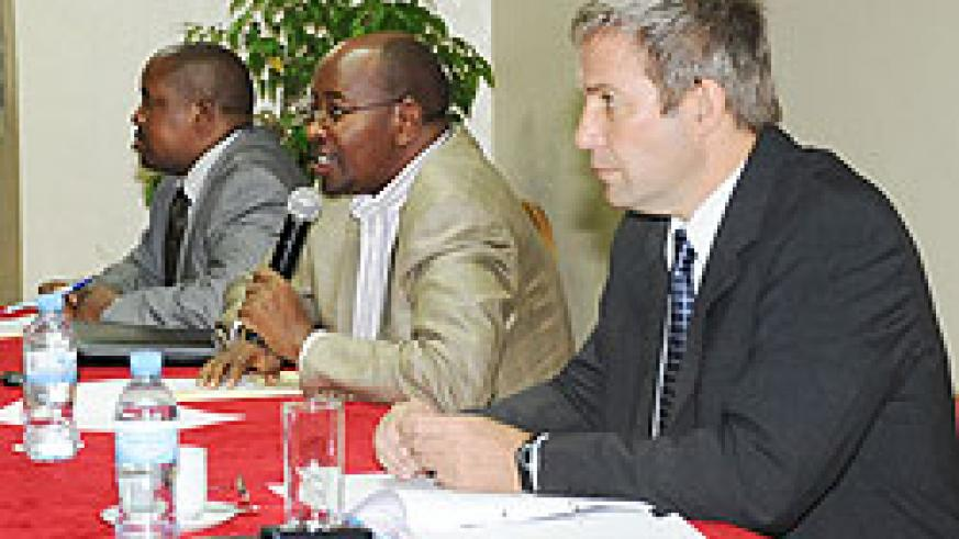 The Minister of Local Government, James Musoni (C) addressing the meeting while Ejide Rugamba (L) and Stephan Klingebeil(R) look on (Photo; T. Kisambira)