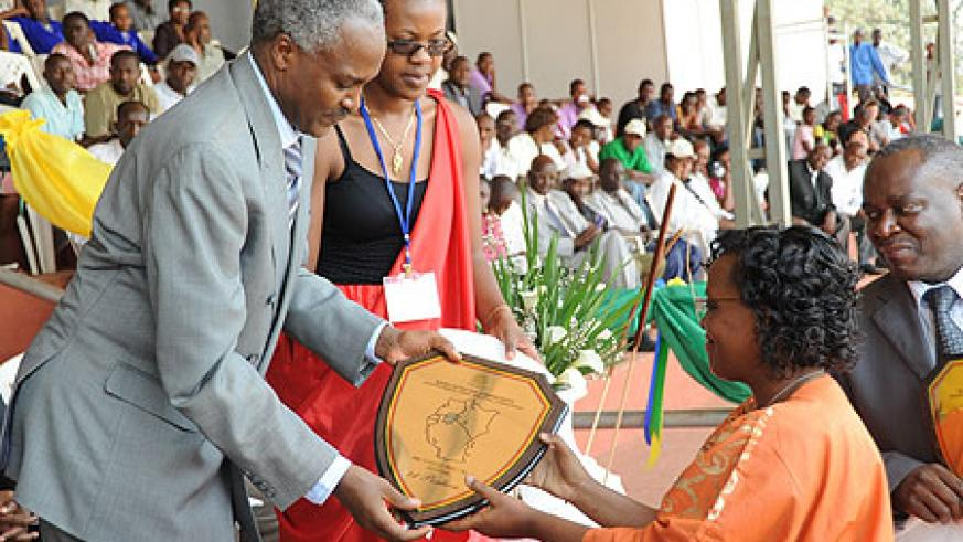 Dr. Charles Murigande awarding a trophy to, Sarah Ingabire, the Headmistress of FAWE girls yesterday (Photo; T. Kisambira)