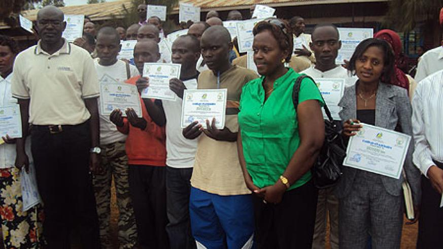 Trainees pose with their certificates in a group photo (Photo; S. Rwembeho)