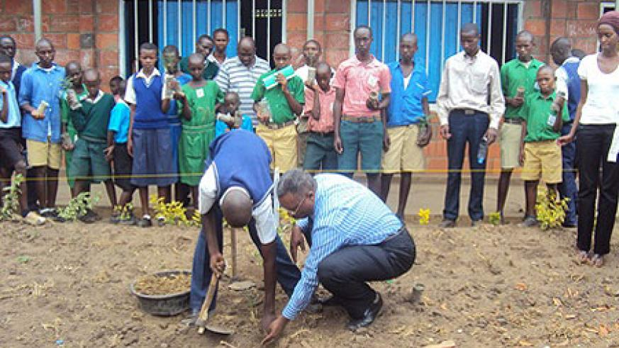 Bralirwa's corporate affairs head, Freddy Nyangezi helping a student plant a tree at the school compound. Photo D Ngabonziza