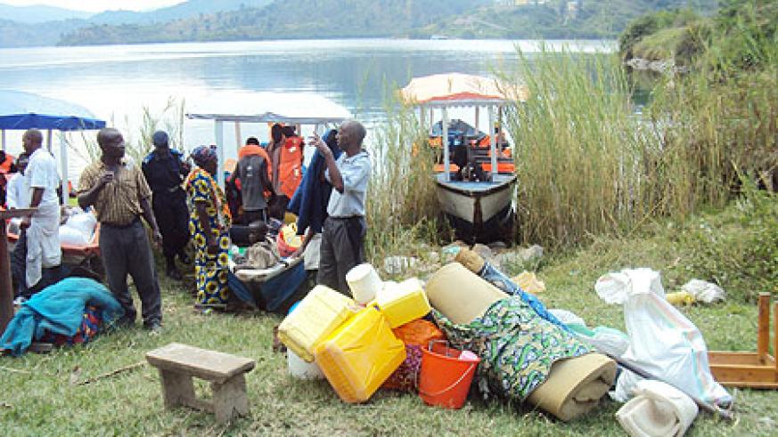 Residents prepare to board awaiting boats upon eviction from the island yesterday (Photo S Nkurunziza)
