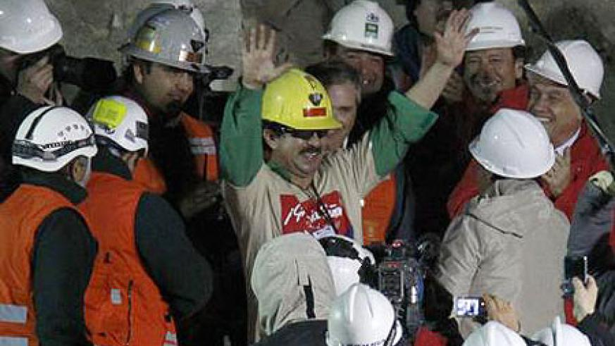 An elated rescued miner waves