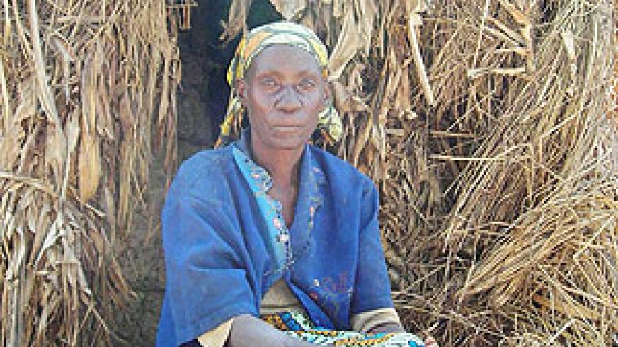 A woman sits infront of her grass thatched hut in Gisagara district, many such dwellings can be found in the Southern Province. (File Photo)