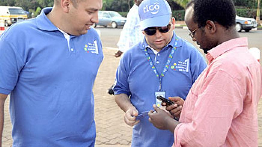 Tigo's top executives Diego Camberos and Marcelo Aleman, the CEO (in middle) sell airtime to a reveller in a recent 'Go Sale' activity (File Photo)