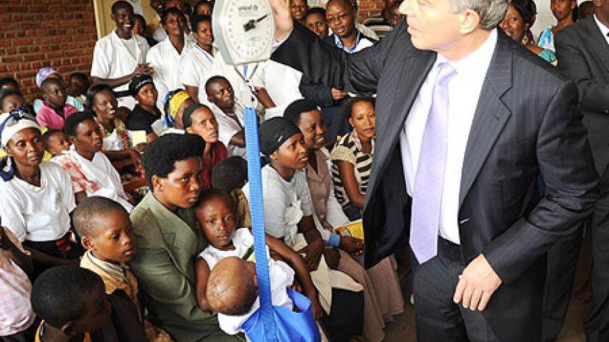 Tony Blair weighing baby Patience Mugabe at Kicukiro Health Centre yesterday (Photo; T. Kisambira)