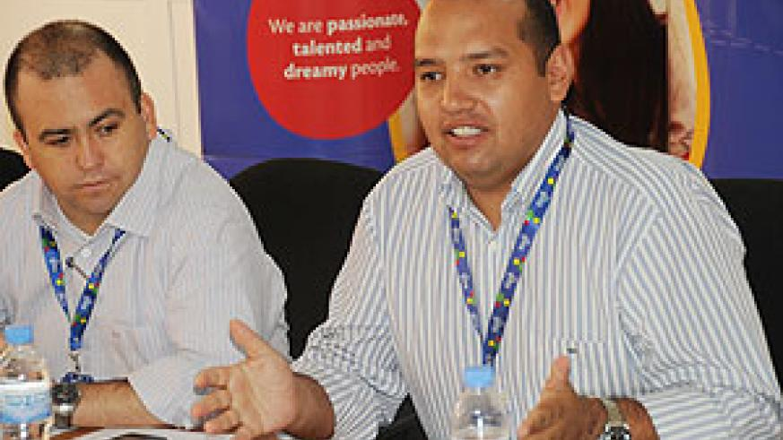 Tigo's Diego Camberos (right) adresses the press recently as the company's CEO look on (File Photo)