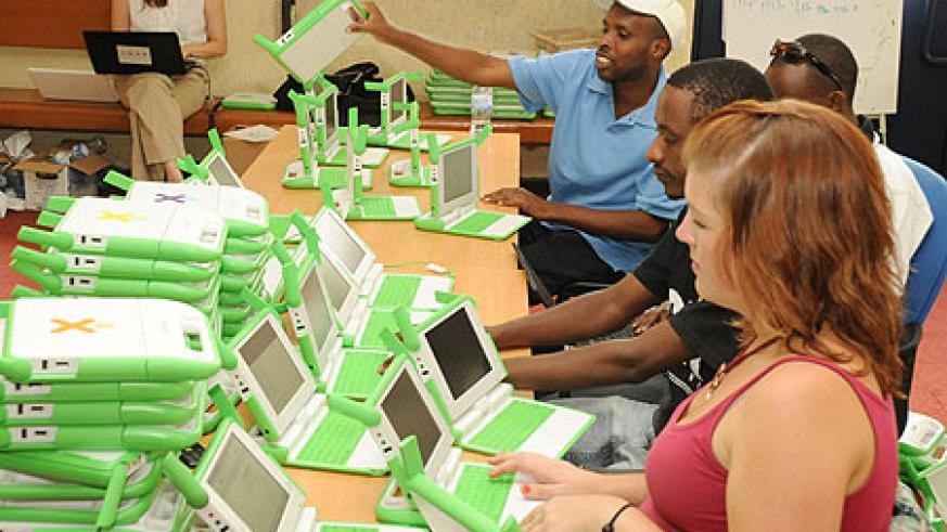 OLPC technicians installing software prior to delivering the laptops to schools (Photo / T. Kisambira)