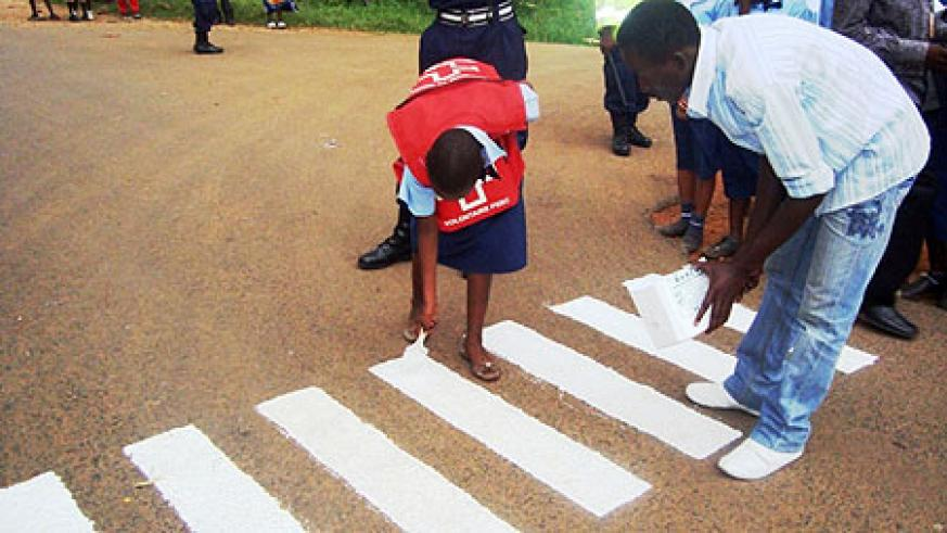 One of the students painting a zebra crossing along Nyagatare-Ryabega road. (Photo.D.Ngabonziza)