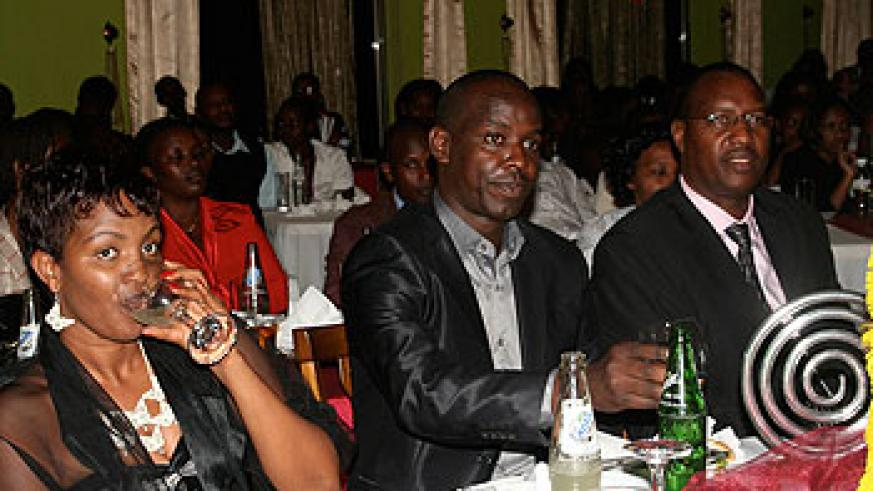 Pastor Alice Mignonne (L) takes a sip while Minister Protais Mitali (Extreme right) watches the action on stage