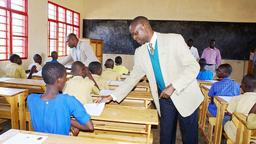 The State Minister for Primary and Secondary Education, distributing question papers to Pupils of Nemba 1 in Gakenke District yesterday (Photo; S. Mugisha)