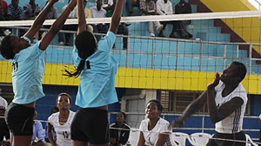 WINNING SPIKE; APR's Dorcus Ndasaba's spike is blocked off court by RRA to help the army retain the Carre'd'AS title. (Photo T. Kisambira)