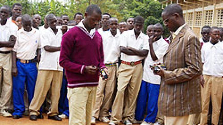 Hon. Harebamungu (R) confiscating students' cell phones in Zaza (Photo; S. Rwembeho)