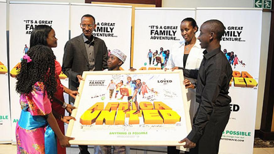 "The President and the First Lady receiving an autographed poster from the cast of the acclaimed movie, ""Africa United"" (Photo Urugwiro Village)"