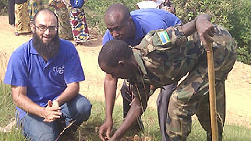 Tigo officials joined by an RDF officer during the tree planting exercise on Monday (Courtsey Photo)