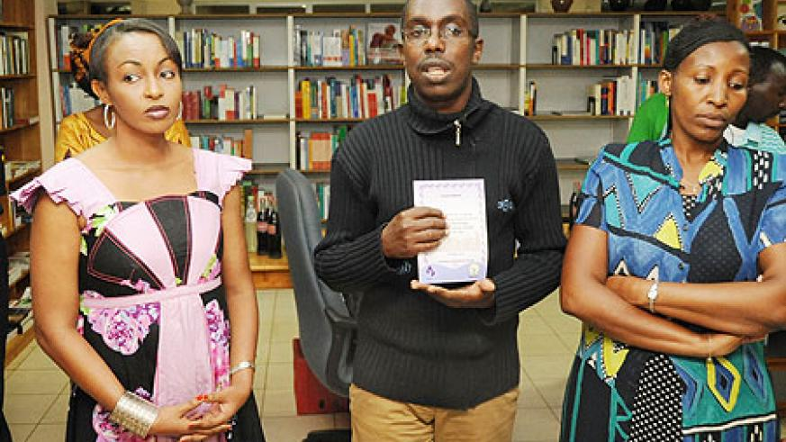 Aimable Kubana (C) shows off his new book. Looking on are some of the Genocide survivors, who were at St. Paul, including RTV's journalist Evelyn Umurerwa (L).