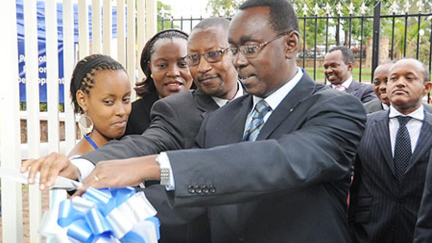 Prime Minister Bernard Makuza cuts the tape as Finance Minister John Rwangombwa, and the Director General of EADB, Vivienne Apopo, look on Photo T.kisambira
