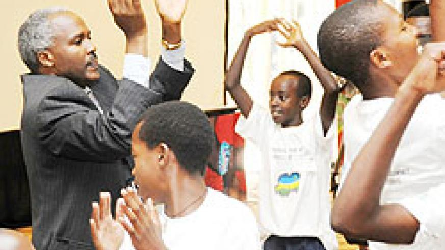 Education Minister, Charles Murigande, joins children in song and dance during the children summit in Kigali yesterday (Photo; T. Kisambira)