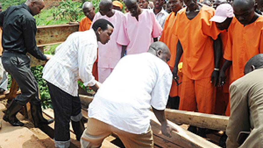 Commissioner General of Prisons Mary Gahonzire (2 left) with other officials join prisoners and residents in the repair of a bridge in Gasabo District