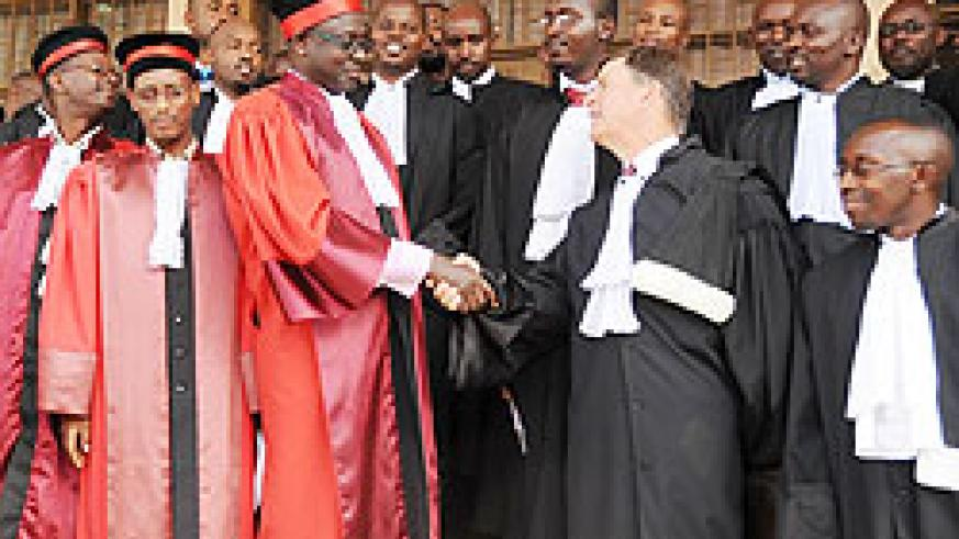 High Court President, Justice Johnston Busingye congratulat,es Tom Allen and other newly sworn in Advocates yesterday (Photo; J. Mbanda)