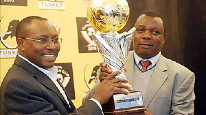 Musonye (r) holds the brand new Cecafa Challenge Cup trophy with sponsor's representative Seni Adetu