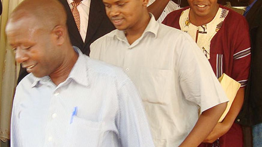 The two suspects, Simpson Mpirirwe (R – in purple shirt), and Didas Ndamiye (C – short sleeved shirt), being led by a Ugandan security official after being handed over, yesterday. Kabale Acting RDC, Vincent Bekunda (in neck-tie) looks on. (Photo B. Asiimw