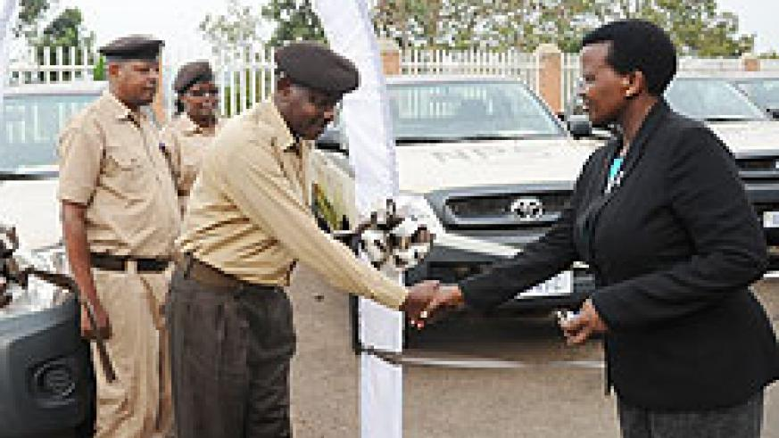 Commissioner General of the National Prison Service, Mary Gahonzire (R), hands over the newly acquired vehicles to Prisons Directors. (Photo J Mbanda)