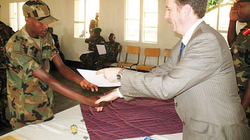 Michael Bibby British council Manager Programmes Rwanda handiing over the certificate to one of the RDF officers yesterday (Courtesy Photo)
